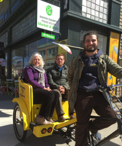 Rebecca Dunn and CFNE Board President Jon Reske ride in a pedicab from worker-owned cooperative Sol Chariots.